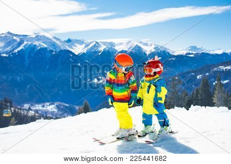 Child Skiing In Mountains. Active Toddler Kid With Safety Helmet, Goggles And Poles. Ski Race For Yo