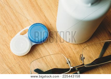 Contact Lenses In Containers, Liquid In Bottle For Eye Care And Glasses On Wooden Table, Top View