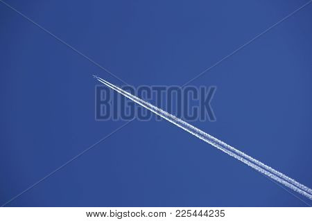 Jet Airliner With Exhaust Vapour Trails In Clear Blue Sky