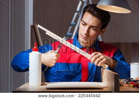 Young man gluing wood pieces together in DIY concept