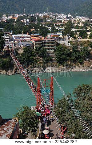 Rishikesh, India - November, 4th, 2017. View Of Ganga River Embankment And Lakshman Jhula Bridge In