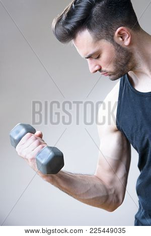 Young Atheltic Man Holding A Smaller Dumbbell In His Hand, Doing Some Arm Warm-up Exercise, Studio I