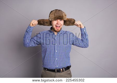 Happy Handsome Young Man In Cap With Earflaps Smiles In Studio.