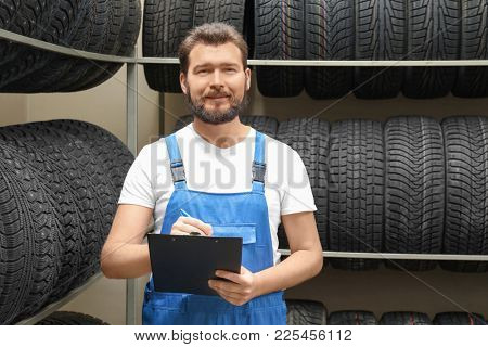 Salesman with clipboard near tires in automobile store