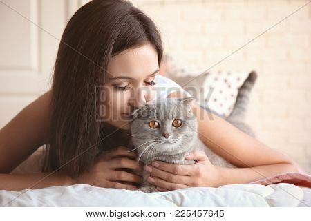 Young woman with cute pet cat on bed at home