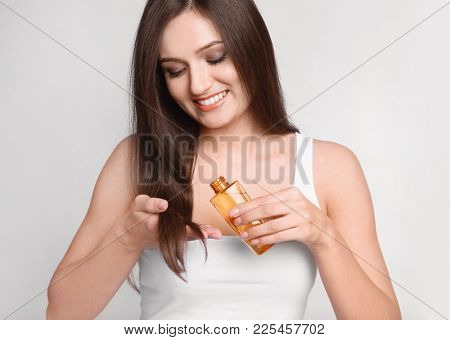 Young woman applying oil onto her hair on light background