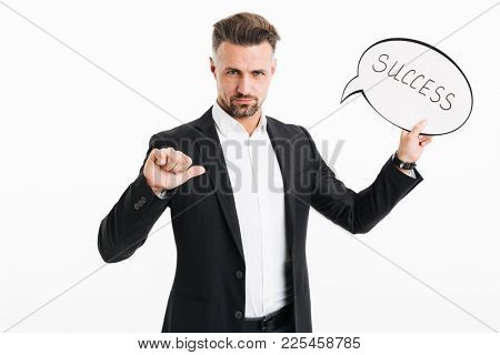 Portrait of a serious mature businessman dressed in suit holding speech bubble with word success and pointing finger at himself isolated over white background