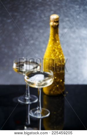 Blurred photo of bottle of wine and two wine glasses on black table