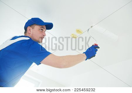 refurbishment. Painter painting ceiling with paint roller poster