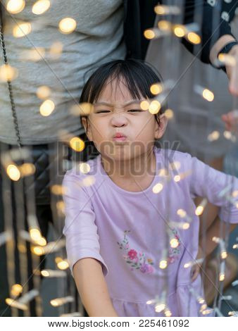 Asain Kid Girl With Funny Face And Chrismas Lightihng Decoration Foreground