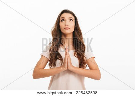 Concentrated brunette woman in t-shirt praying with pray gesture and looking up over white background