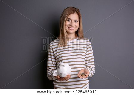 Young woman with broken piggy bank and coins on grey background