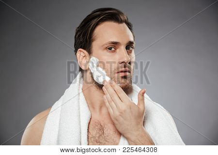 Headshot of healthy man putting shaving foam on face while having morning skincare isolated over gray backgroung
