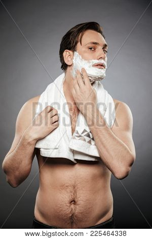 Full-length photo of half naked adult guy putting shaving foam on face with towel on his neck isolated over gray backgroung