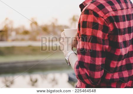 Man Hold Coffee Cup In Hand Stand Alone Near The Lake With Morning Light Selective Focus, Copy Space
