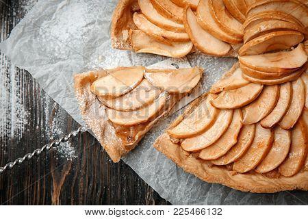 Tasty cut apple tart on wooden table, closeup