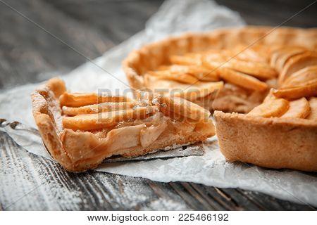 Tasty apple tart on wooden table, closeup