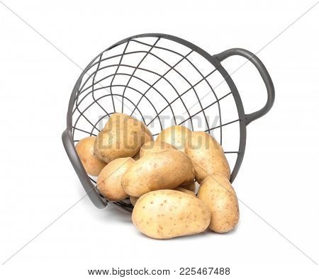Overturned basket with fresh raw potatoes on white background