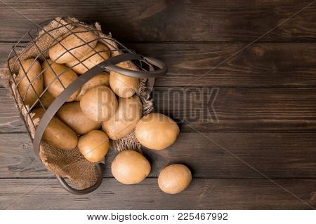 Overturned basket with fresh raw potatoes on wooden background, top view