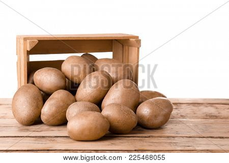 Overturned wooden container with fresh raw potatoes on table against white background