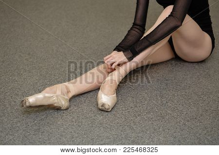 The Ballerina Ties The Tapes With Pointe Shoes. Long Slender Female Legs. Beautiful Graceful Hands.
