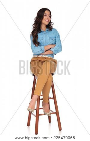 smiling seated casual woman looks away with hands crossed on white background