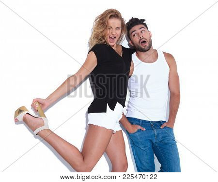 super excited woman pulls man's hairs and holds her heel while he stands with hands in pockets on white background