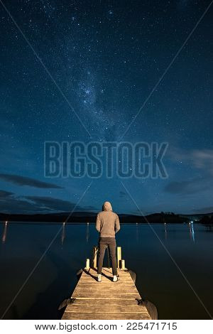 Young Male Photographer Taking Photo Of Milky Way On Jetty By The Lake At Night Time. Stargazing Pho