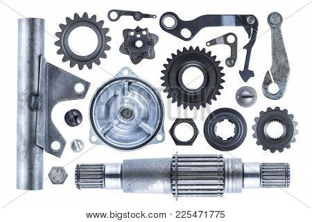 A Large Collection Of Steel Engine Parts Including Gears, Shafts, Bolts, And Other Various Elements.