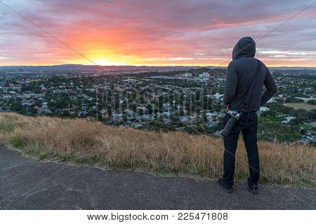 Anonymous Photographer Man Wearing Hoody Watching Sunrise Over Auckland City At Mount Eden View Poin