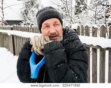 Winter. An elderly man leans on a snow shovel