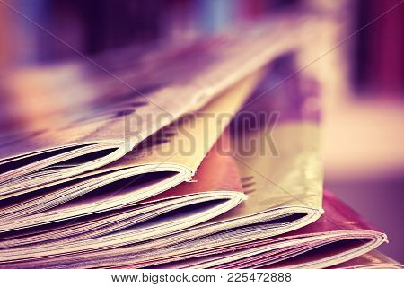 Close Up Edge Of Colorful Magazine Stacking With  Blurry Bookshelf Background For Bublication And Pu