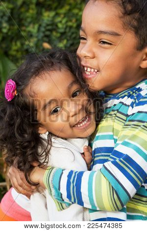 Hispanic Brother And Sister Laughing And Hugging.