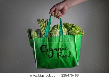 Close Up A Hand Holding Green Grocery Bag With Organic Food Text Of Mixed The Organic Green Vegetabl