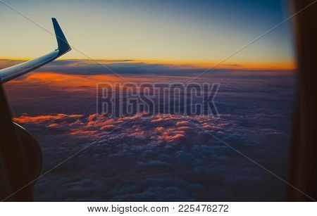 Beautiful View From The Window Porthole. The Wing Of An Airplane On Sunset Sky Background With Cloud