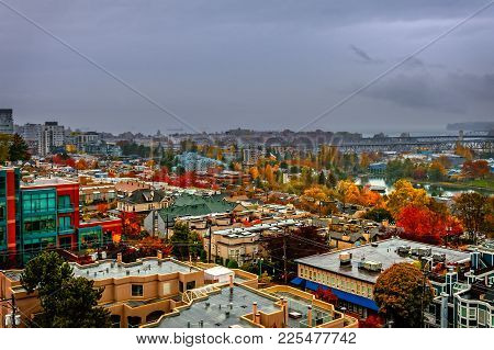 Top View Of A Modern Beautiful City With Red, Yellow And Green Trees, A River, A Bridge, High-rise B