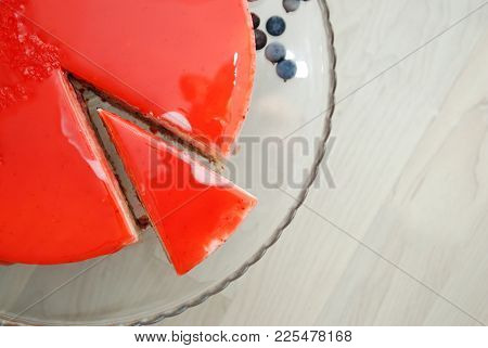 A Piece Of Red Strawberry Cake Covered With Mirror Red Glaze. Top View