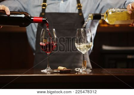 Male Sommelier Pouring Red And White Wine Into Long-stemmed Wineglasses. Waiter With Two Bottles Of