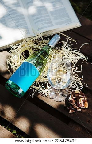 Glasswine With White Wine, Bottle And Pieces Of Chocolate Lies On Sawdust Near Big Open Book, Romant