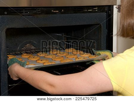 Close up on young female hands pulling tray of soft and chewy chocolate chip cookies out of the oven