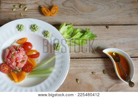 Red Fish Fillet With Cherry Tomato Salad, Celery And Pumpkin Seeds And Dressing On A Wooden Table, T