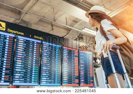 Asian Teenage Girl Is Using A Smartphone To Check Flight At The International Airport To Travel On W