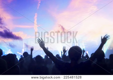 Praise And Worship Concept: Silhouette Christian People Hand Rising Over Blurred Cross On Spiritual