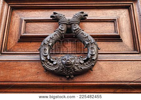 Old Metal Door Handle Knocker On Wooden Background.