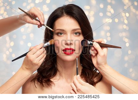 beauty and people concept - beautiful young woman with red lipstick and hands of make up artists with brushes over holidays lights background