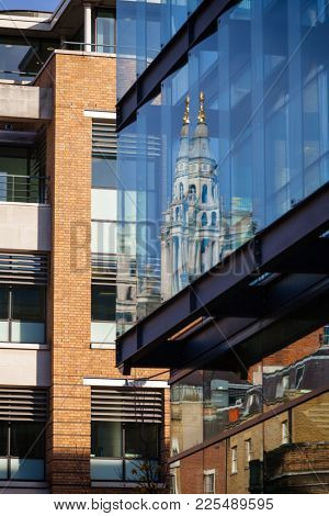 St Paul's Cathedral tower reflecting in a window of contemporary office building London UK