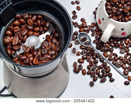 Electric Coffee Grinder With Roasted Coffee Beans Inside And Coffee Beans Scattered On A Table With