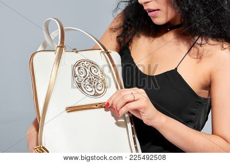 Close Studio Photo Of A Model Carrying White Bag With A Golden Pattern, Handles And A Little Zipper.