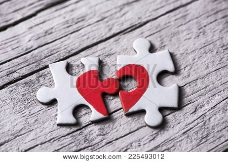 closeup of two separated pieces of a puzzle which together form a heart on a white rustic wooden surface, depicting the idea of rupture or cooperation