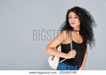 Sexy Young Girl With Black Curly Hair Carrying White Backpack With A Golden Zipper. She Wears Black